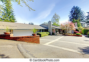 One level house with large parking area and spring landscape.