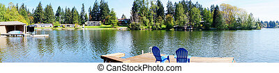 Lake waterfront with pier and blue chairs and spring trees -...