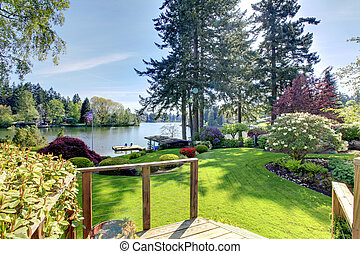 Lake view backyard with deck and spring landscape.