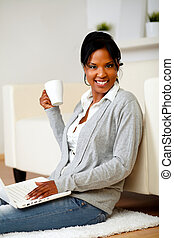 Young woman with a mug in front of her laptop