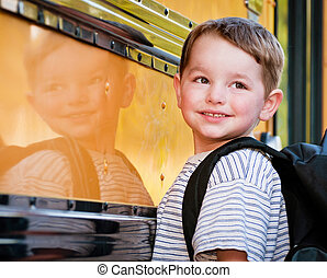 Young boy in front of school buss - Young boy with nervous...