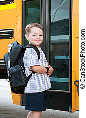 Boy in front of school bus - Happy young boy in front of...