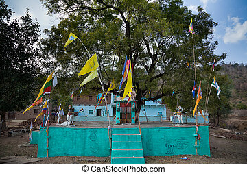 Temple in indian village on hill, many colorful flag on...