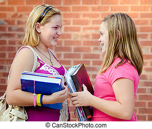 Two adolescent or teen girls talking outside school during...