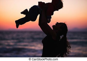 Silhouette of mother throwing baby up on sunset