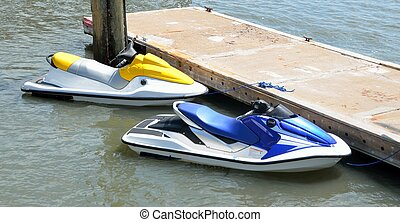 Wave runners parked at a dock - Jet ski moored at a dock in...