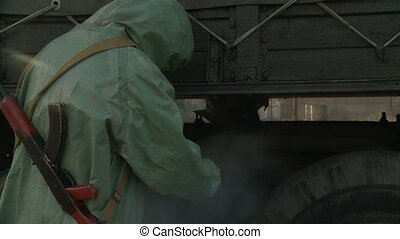 Soldier in overalls disinfecting truck - View of military...