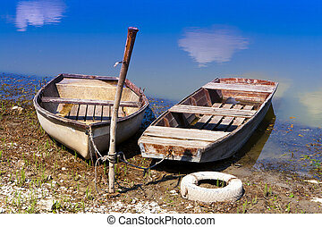Two empty boat on the shore. - Boats anchored to the shore.