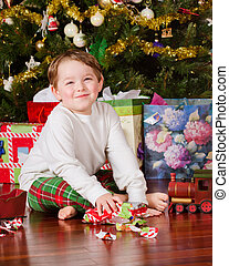 boy unwrapping presents - Young boy unwrapping presents on...
