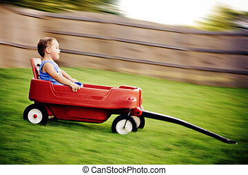 Young boy zooms downhill in wagon in image with motion blur