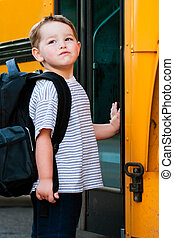 Boy in front of school bus