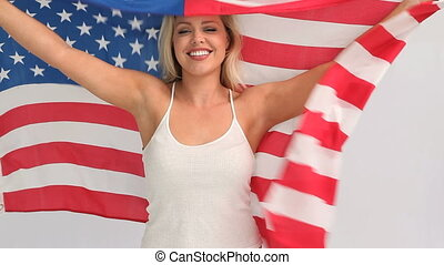 Blonde woman holding a USA flag against a grey background