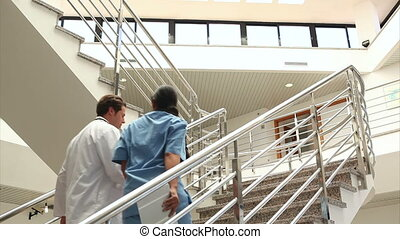 Doctor and nurse in the stairs in hospital