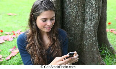 Woman texting in a park