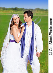 Couple in wedding day hug in green meadow