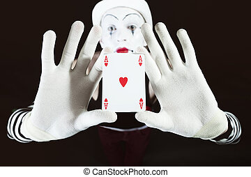 Funny mime holding a ace of hearts on black background