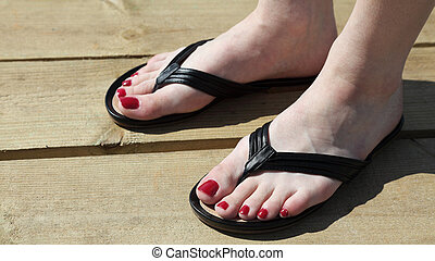 Female feet with flip-flops red nail - Female feet with...