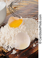 Egg yoke and baking mix - An egg yoke in the shell on a...