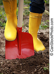 Digging soil with a shovel - A woman in yellow boots is...