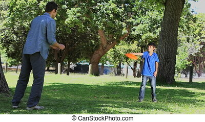 Son with his father playing frisbee - Video of a son with...