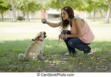 Cute dog owner playing with her pet - Young beautiful woman...