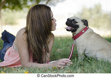 Blowing a kiss to her dog at a park - Young beautiful woman...