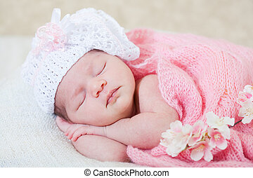 newborn girl sleeps with spring flowers under a knitted pink...