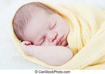 sleeping newborn baby wrapped in a yellow blanket