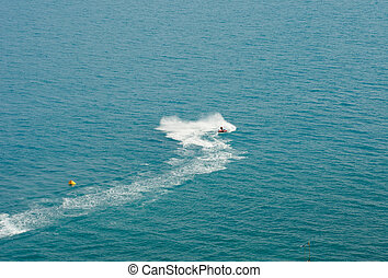 white trace water motorcycles on blue sea surface