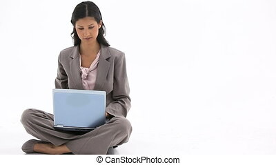 Woman sitting while using a laptop