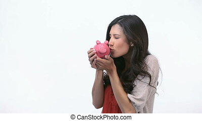 Happy woman kissing a piggy bank - Video of a happy woman...