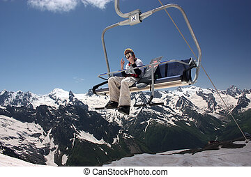 Skier on the ski lift - People skiing and ski lift on...