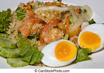 Seafood fried rice - Rice with seafood in white plate .