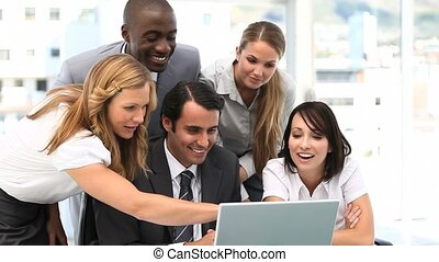 Business team looking at a laptop - Video of a business team...