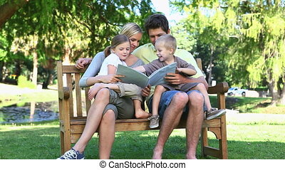 Family sitting on a bench reading a