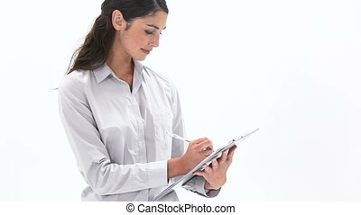 Woman writing on a notepad - Video of a woman writing on a...