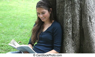 Woman reading a book while sitting