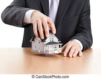 Businessman holding house architectural model