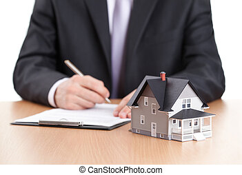 Businessman signs contract behind home architectural model -...
