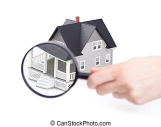 Hand holding magnifying glass in front of the home