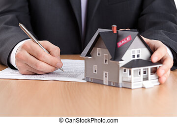 Real estate concept - businessman signs contract behind...