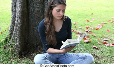 Woman reading a book next to a tree