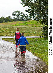 Little boy splashing in a puddle - little boys splashing in...