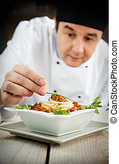 Male chef in restaurant kitchen is garnishing and preparing...