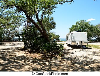 RV Camping - RV trailer camped at a site along the river's...