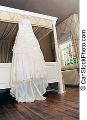 ivory wedding dress on four poster bed