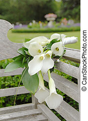 calla lily - clla lily draped over a wooden bench