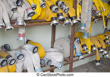 Yellow firehose are hanging on warehouse shelfs - Yellow...