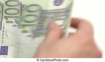 Euro bills displayed by a hand on a white table