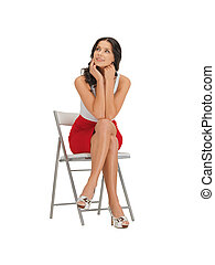 woman in dress - happy woman in dress on a chair